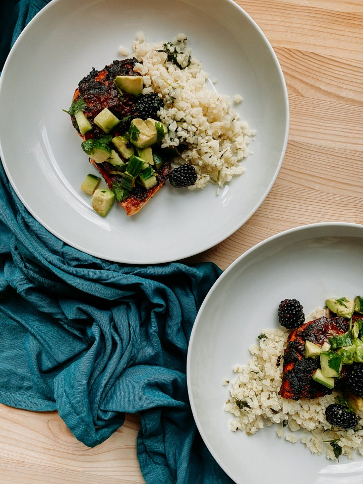 a blue towel with two white bowls that have spicy salmonw ith adobo sauce and a green salsa of blackberries, avocado, and cucumber inside