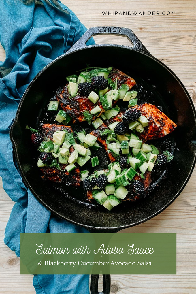 a wooden surface with a cast iron pan with seared salmon with adobo sauce and green salsa resting on a blue towel