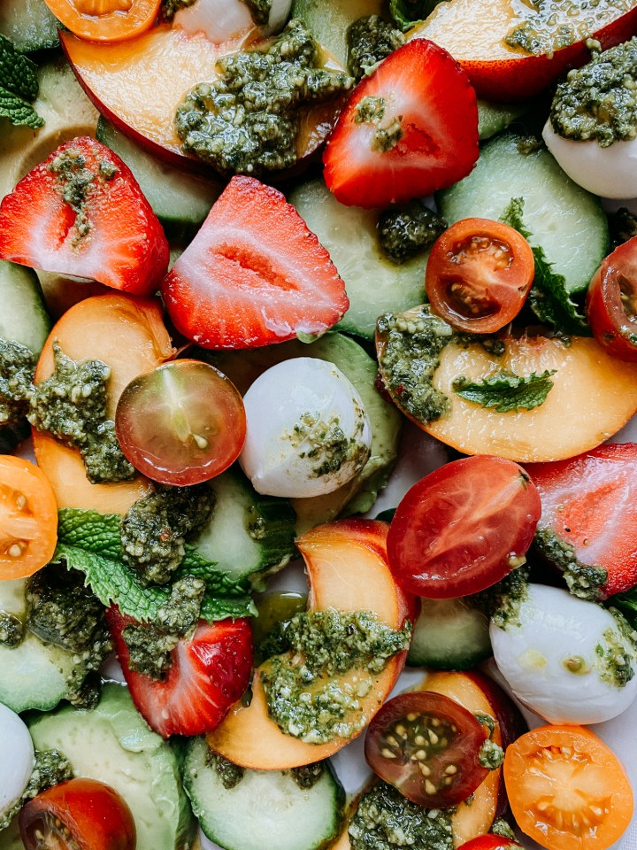 closeup of mozzarella balls, sliced strawberryies, sliced peaches, cucumbers, avocado slices, sliced tomatoes, and pesto