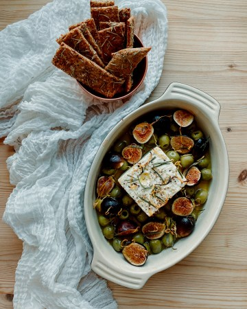Baked Feta with Green Olives and Figs i a baking dish surrounded by cheesecloth and a dish of sourdough discard crackers on a wooden surface