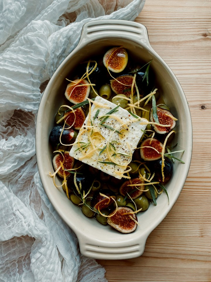 Baked Feta with Green Olives and Figs resting in a baking dish on a piece of white fabric on a wooden surface
