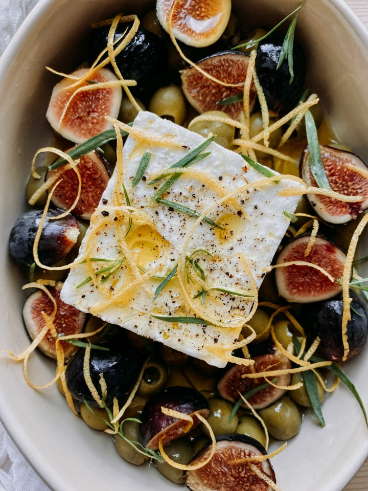 closeup of lemon peel and olive oil on a block of feta with green olives and figs arranges around the cheese in a baking dish