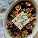 figs, green olives, and feta cheese that have been baked together in a le creuset baking dish resting on a piece of white fabric