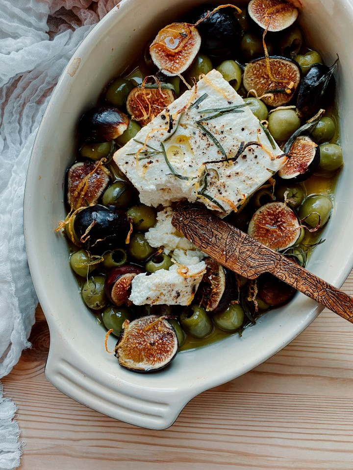 a wooden cheese knife resting in a dish with figs, feta cheese, and green olives covered in herbs and olive oil