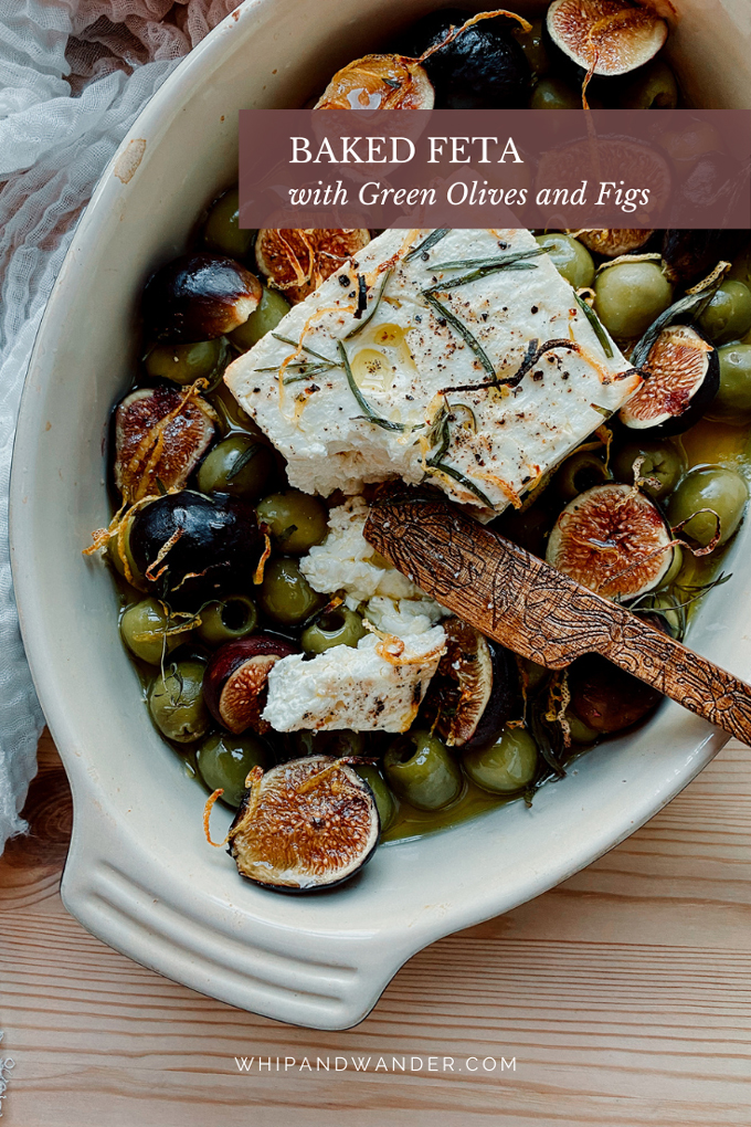 a baking dish that contains baked feta, figs, and green olives that have been baked together. a wooden cheese knife is resting in the dish