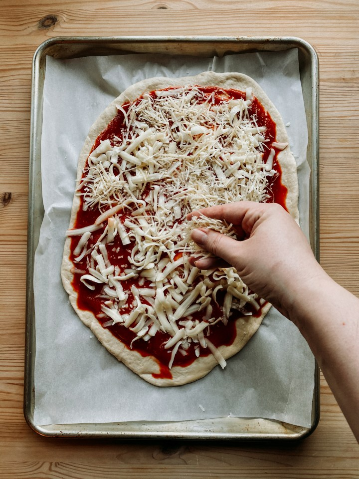 a hand sprinkling parmesan cheese on pizza dough