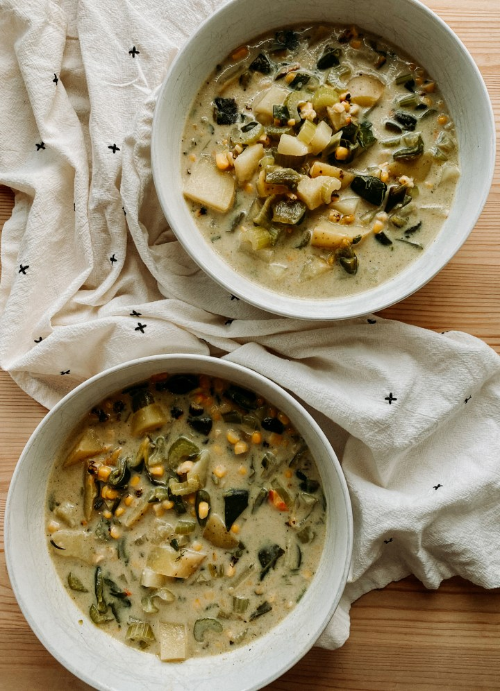 Roasted Poblano Corn Chowder in two large white soup bowls resting on a white towel