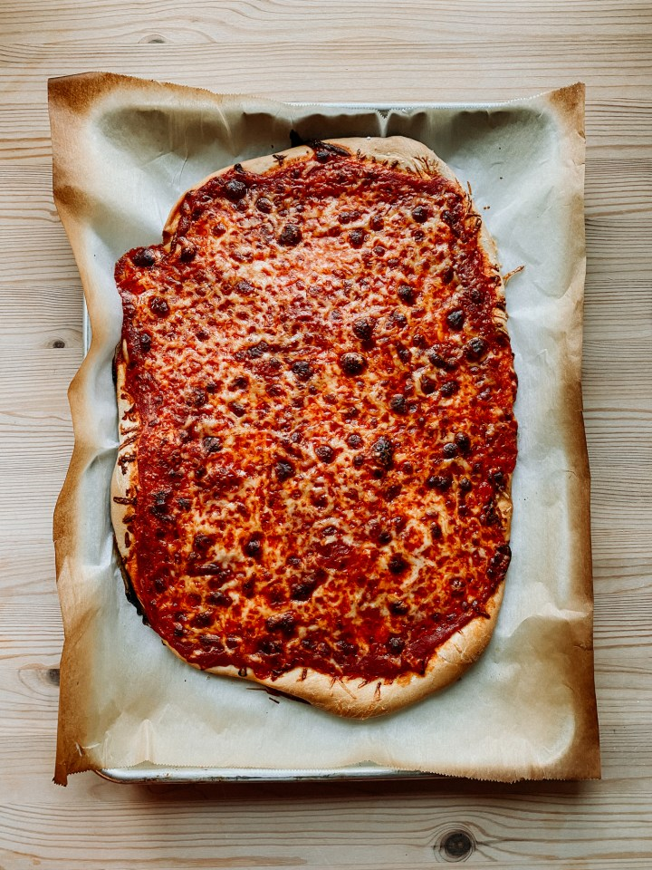 a baked cheese pizza resting on a parchment lined baking sheet on a wooden surface