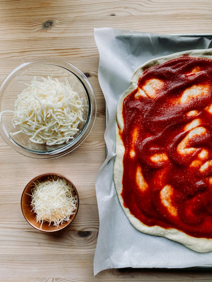 a sheet pan with a rolled out piece of pizza dough with sauce resting next to two bowls containing mozzarella and parmesan cheese