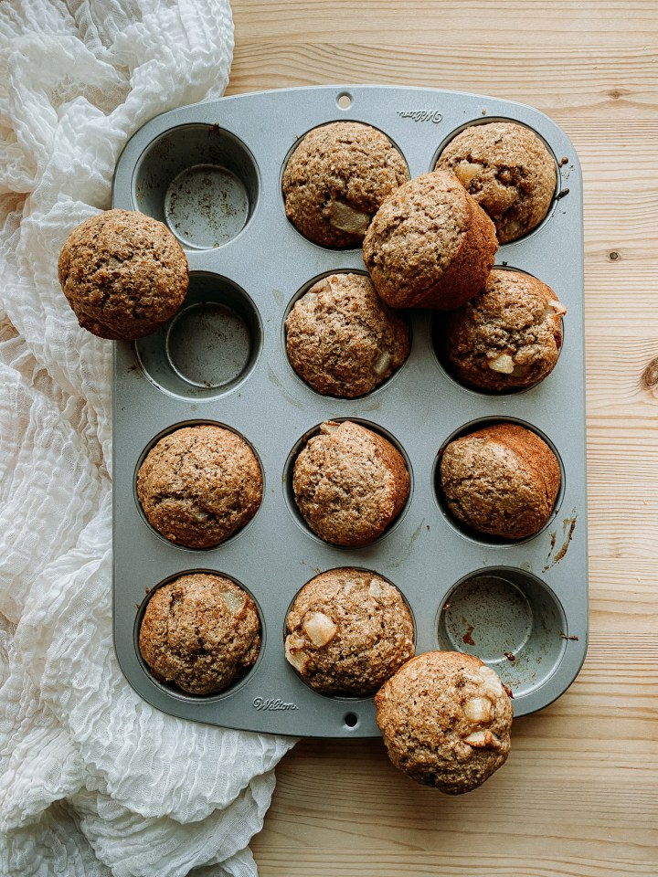a baking tin filled with Sourdough Discard Spiced Pear Muffins resting on a piece of cheesecloth on a wooden surface
