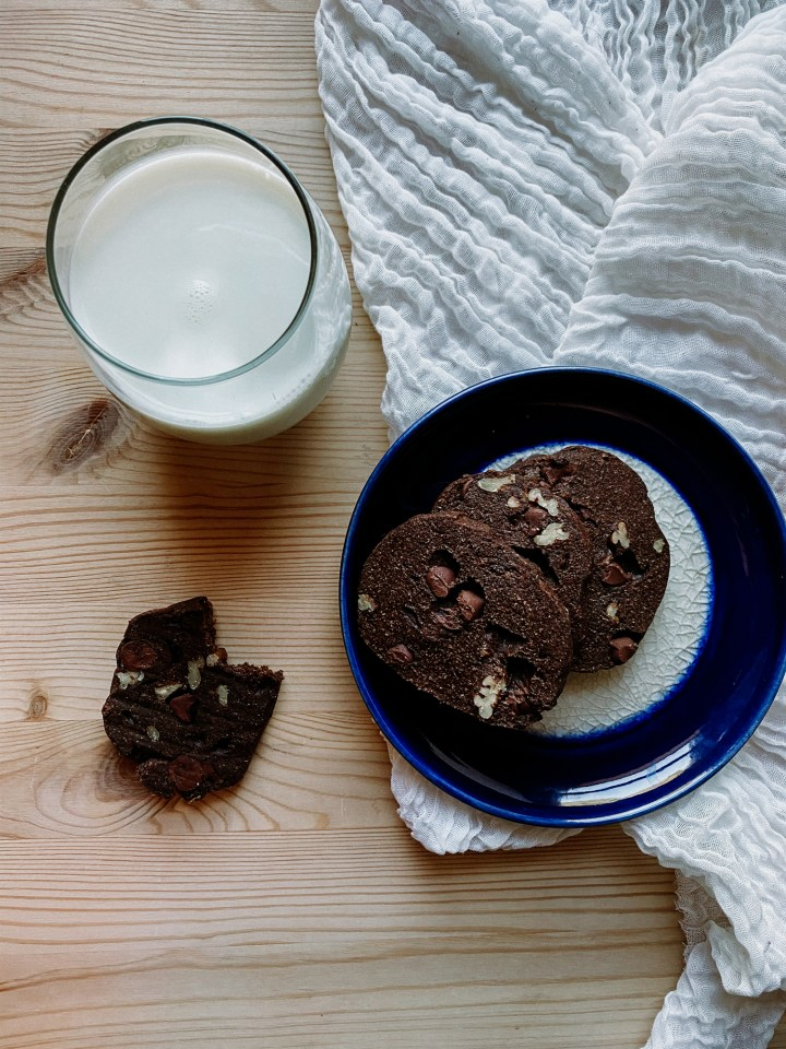 a glass of milk sitting next to a blue plate of chocolate biscuits on a white piece of fabric resting on a wooden surface