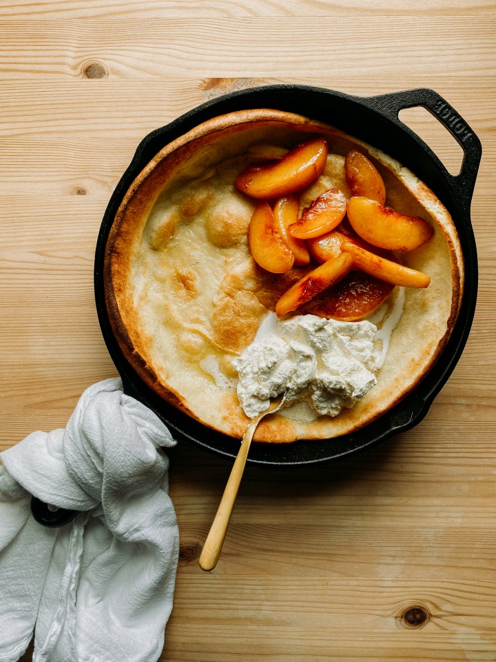 Peaches and fresh whipped cream on top of a Buttermilk Dutch Baby in a cast iron skillet resting on a wooden surface