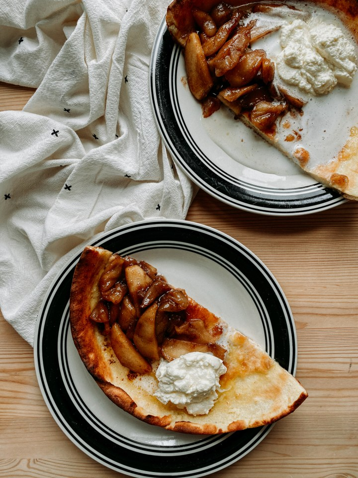 two white and black plates resting on a wooden tabletop with halves of Buttermilk Dutch Baby with spiced apples and whipped cream on top