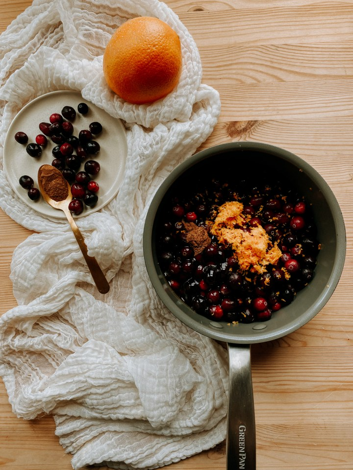 a medium saucepan with cranberries, orange juice, honey, orange zest, and cinnamon inside resting on a wooden surface with a neutral cloth. The ingredients resting on a small plate nearby along with a whole orange