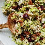 a wooden spoon scooping into a Shaved Brussels Sprouts Salad with Blue Cheese, pecans, and cranberries