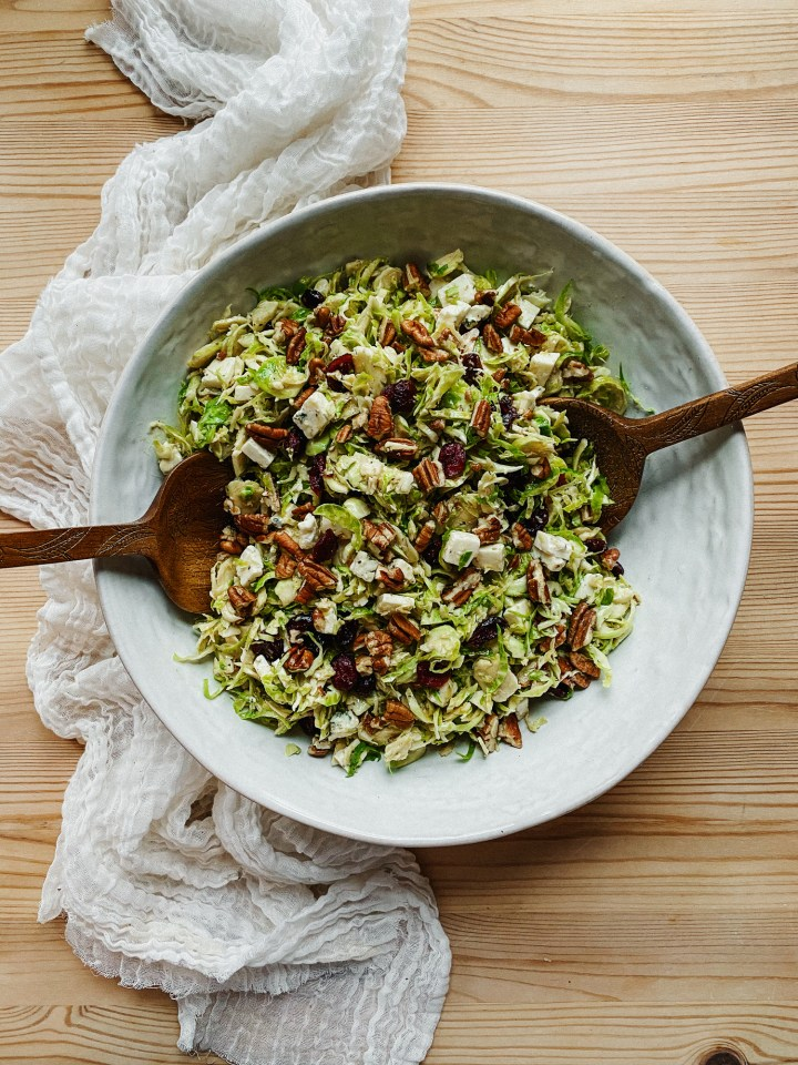 salad serving tongs in a white bowl of shaved brussels sprouts salad resting on a wooden surface
