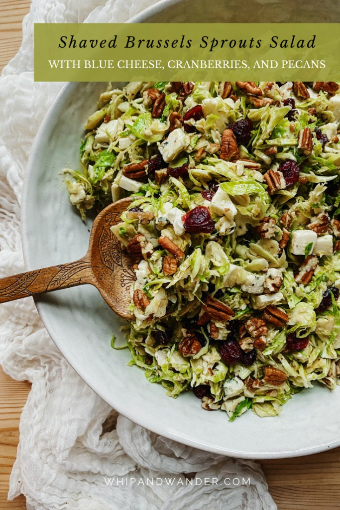 a salad with brussels sprouts, cranberries, blue cheese, and dijon dressing in a white dish