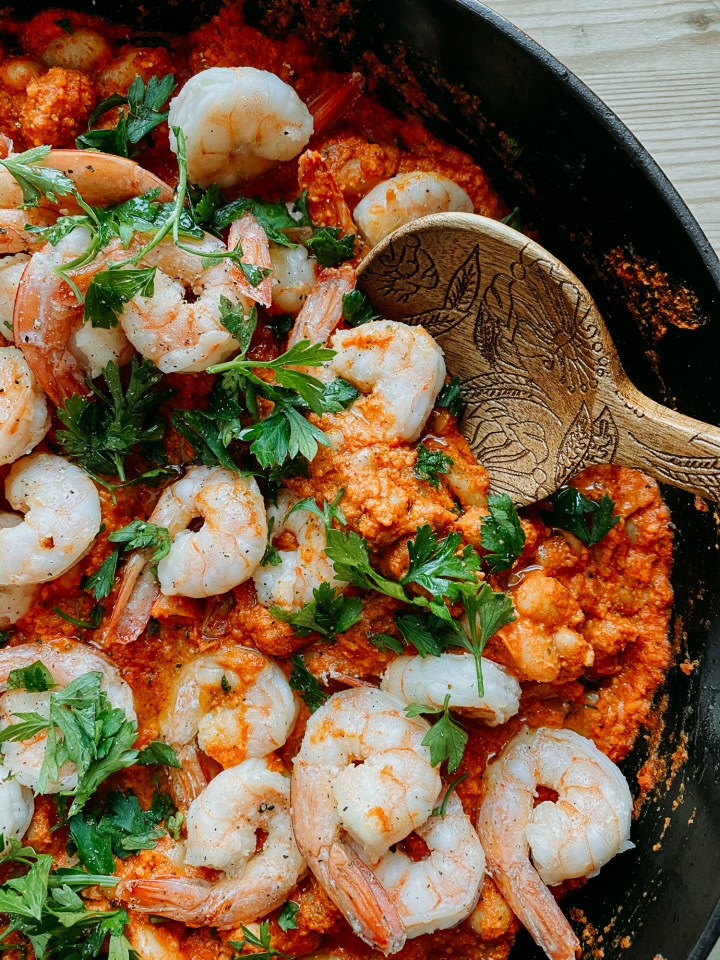 a wooden spoon scooping into Shrimp in Romesco Sauce with White Beans and parsley