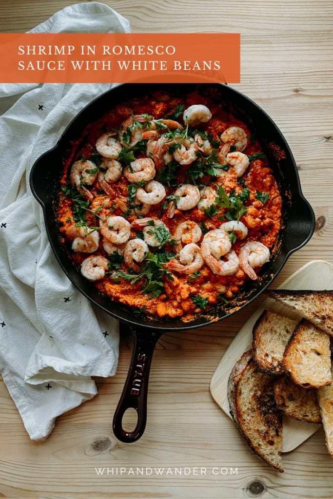 a red skillet of Shrimp in Romesco Sauce with White Beans resting on a wooden surface with a white towel and a board full of toast