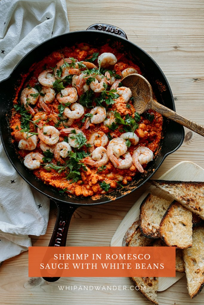 a skillet filled with Shrimp in Romesco Sauce with White Beans topped with fresh parsley and a wooden spoon scooping into the skillet, a tray of toast resting nearby