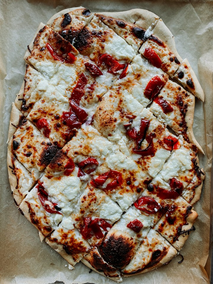 a White Pizza with Hot Pickled Peppers and Honey that has been sliced into squares