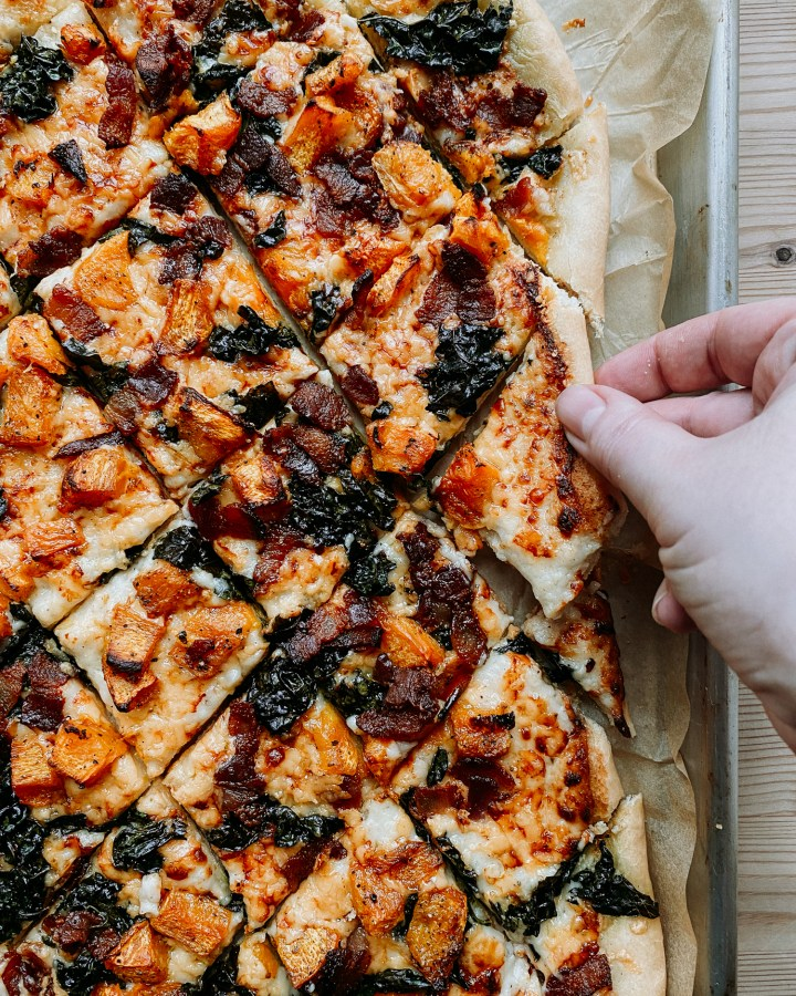 A hand pulling a slice of White Pizza with Pumpkin, Bacon, Kale, and Gouda from the larger pie on a tray