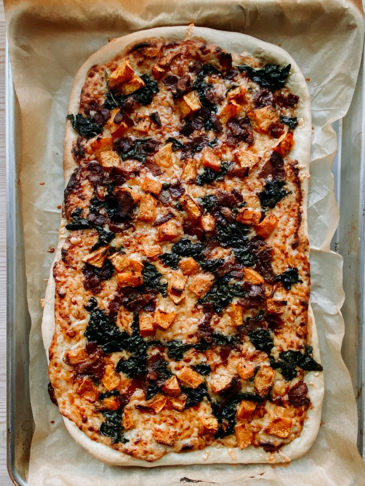 a baked White Pizza with Pumpkin, Bacon, Kale, and Gouda on a piece of brown parchment paper