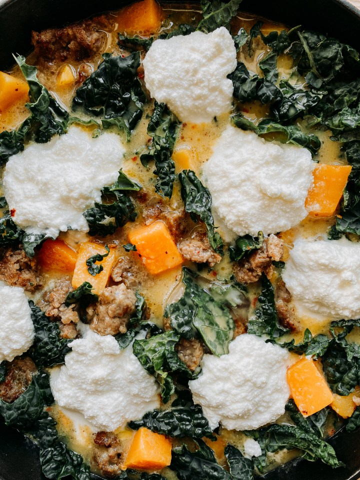 closeup of unbaked eggs, butternut squash, sausage, kale, and ricotta