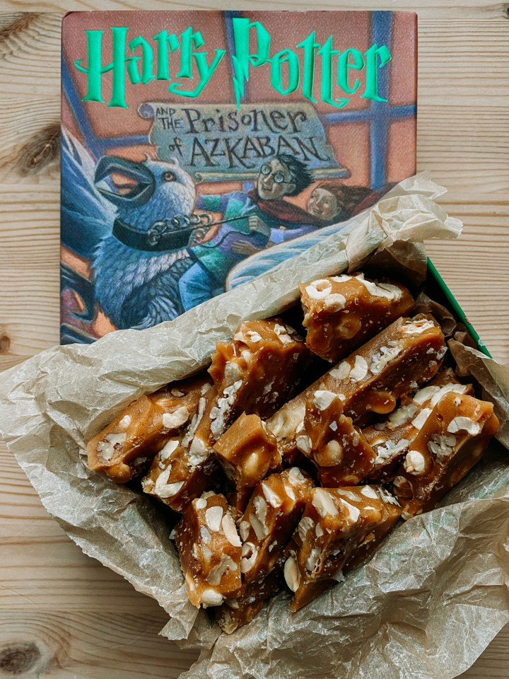 Chunks of Molly Weasley's Nut Brittle in a small tin resting on top of the book harry potter and the prisoner of azkaban