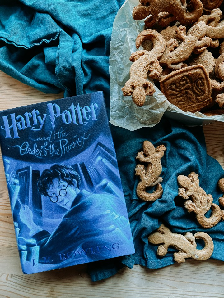 a blue harry potter book resting on top of a dark teal towel with several newt shaped ginger biscuit cookies on top