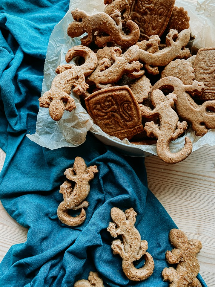 gingersnap biscuits in the shape of lizards and hogwarts crests in a cookie in with several more biscuits on tp of a teal towel