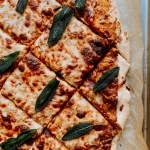 a Pumpkin Pizza with Gruyere and Crispy Sage that has been sliced into squares resting on a parchment lined baking sheet