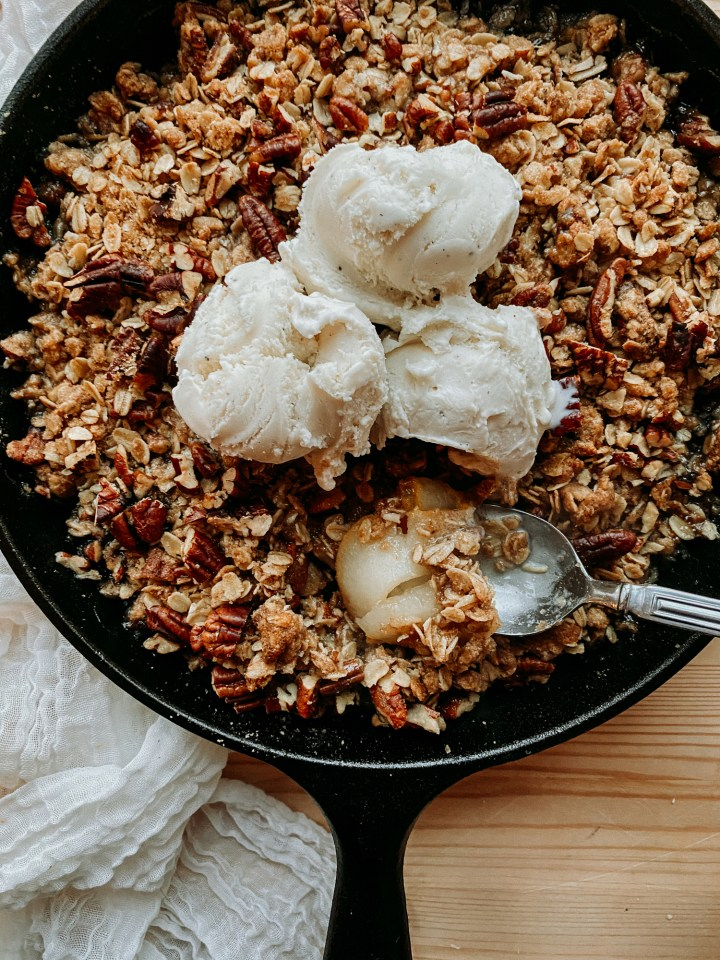 a spoon resting in a cast iron pan of Spiced Pear Crisp that contains three scoops of vanilla ice cream