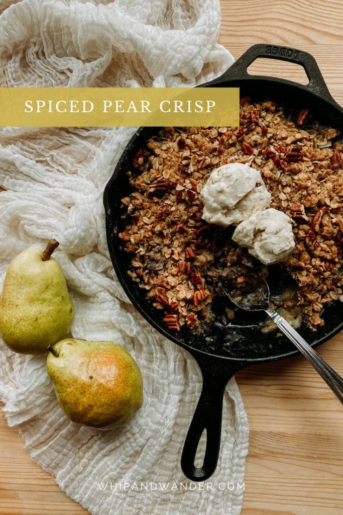 a vanilla ice cream topped pear crisp with spices in a cast iron pan with a spoon resting in the pan and two fresh pears resting next to the dish on a wooden table with a piece of cream colored cloth