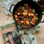 a large dutch oven pot with Yule Ball Beef Goulash resting next to the book harry potter and the goblet of fire in a wooden surface with a white piece of fabric