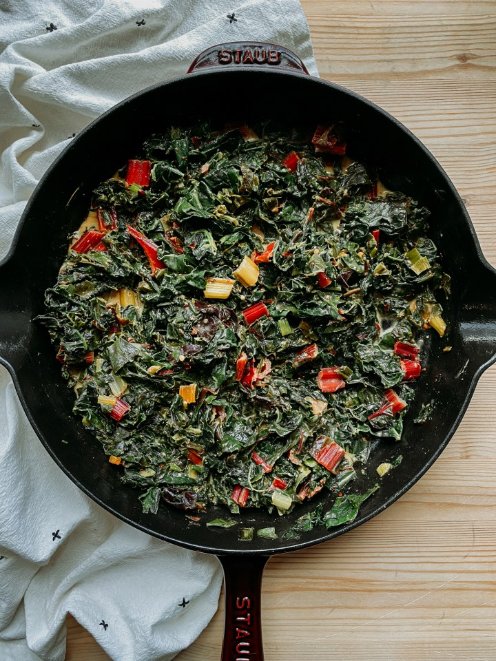 a skillet filled with Dijon Creamed Greens on a woodne table with a white towel under the pan