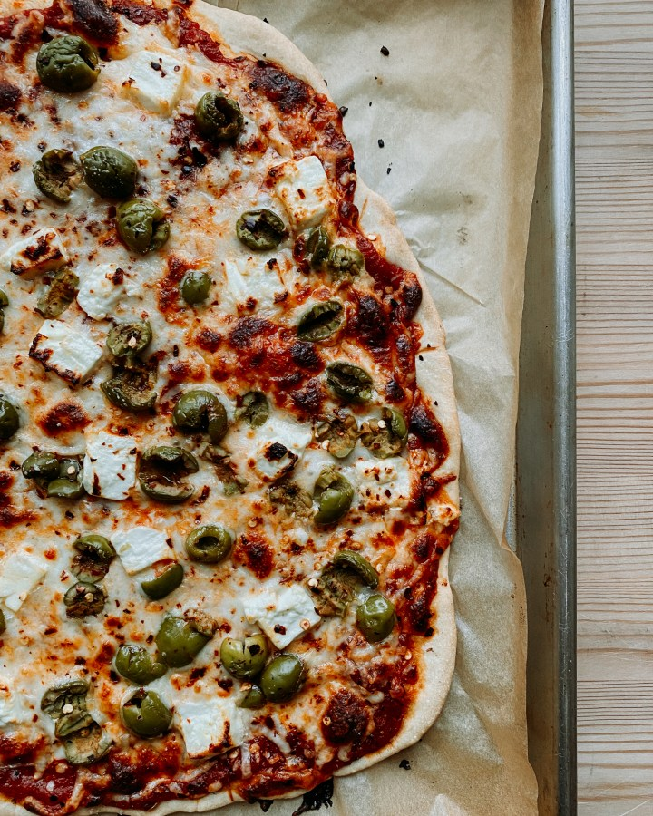 Green Olive and Feta Pizza resting on a parchment lined baking sheet resting on a wooden table