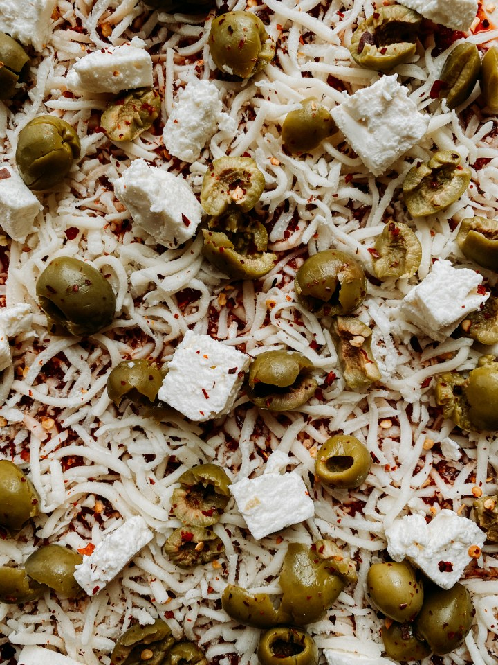 closeup of green olives and cubes of feta and shredded mozzarella on a red sauce topped pizza dough crust