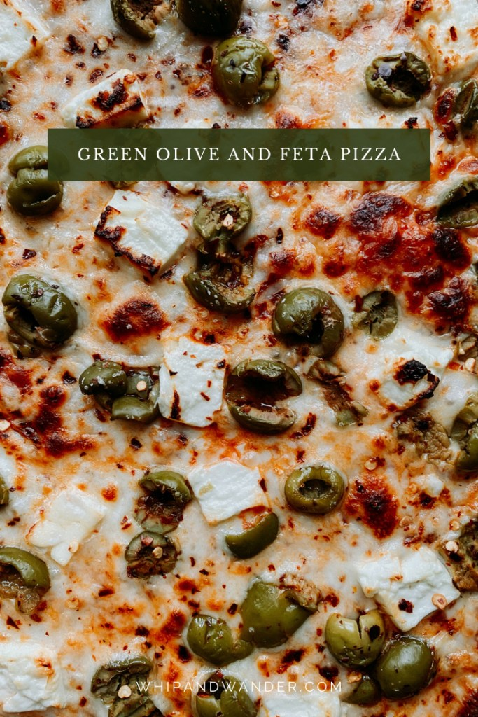 closeup of green castelvetrano olives, charred feta cubes, and red pepper flakes on a pizza