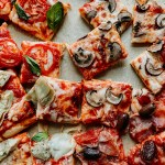 squares of pizza topped with mushrooms, prosciutto, olives, artichoke hearts, tomatoes, and basil