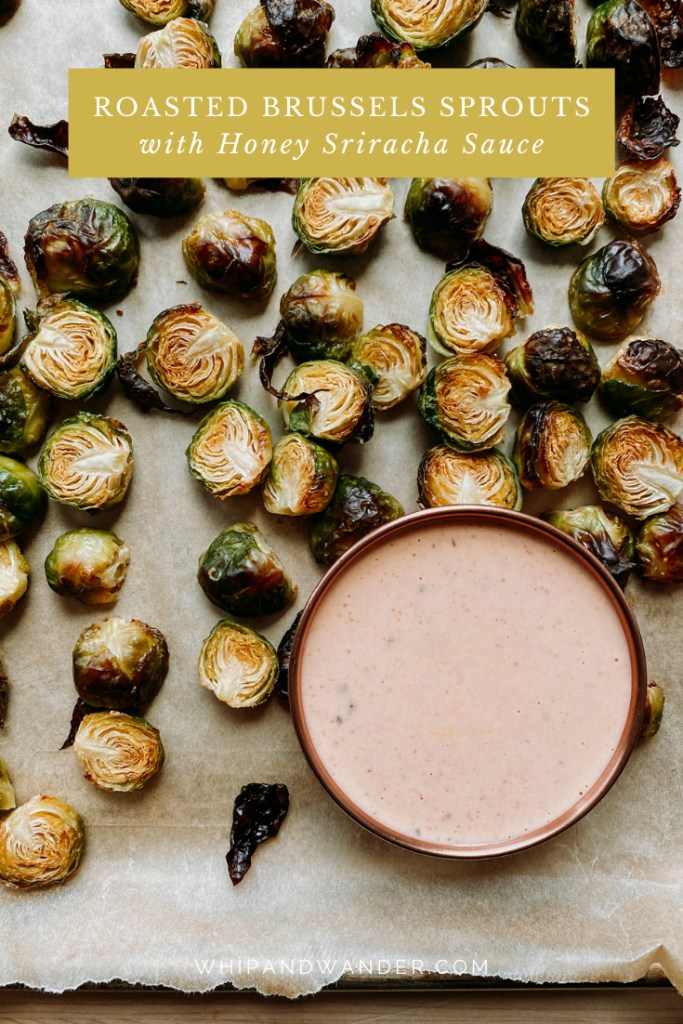 a copper bowl of creamy honey sriracha sauce that is resting on a bakers tray with roasted brussels sprouts