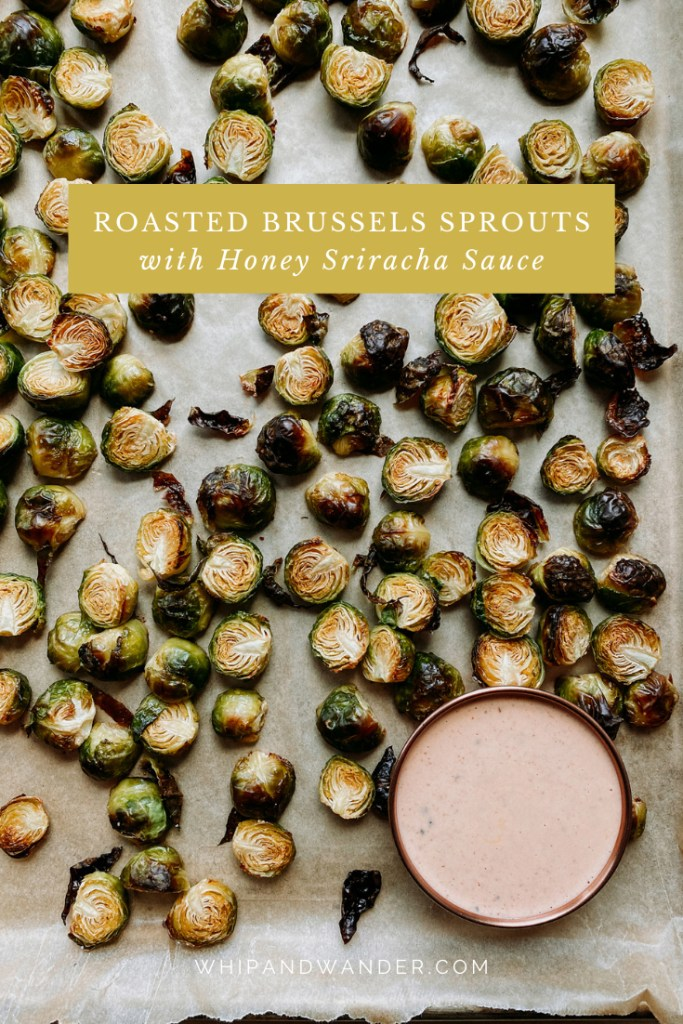 a bowl of yogurt and mayo base honey sriracha sauce resting on a sheet pan with roasted brussels sprouts