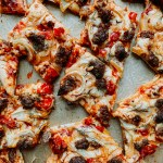 square pieces of Sausage, Fennel, and Calabrian Chili Pizza on a parchment lined baking sheet