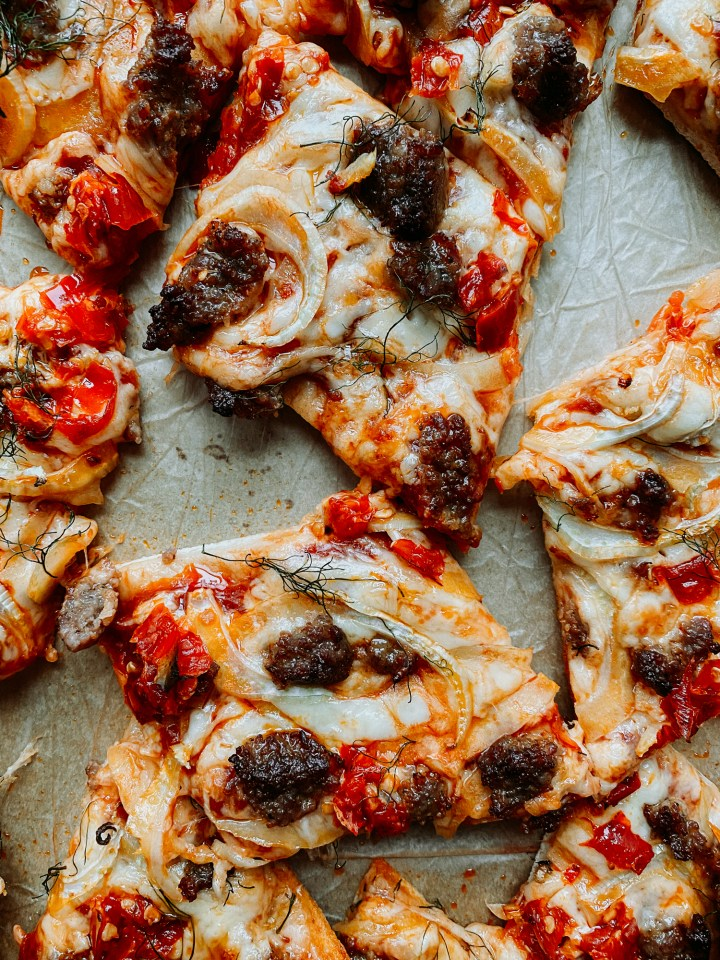 closeup of square slices of Sausage, Fennel, and Calabrian Chili Pizza in a baking sheet