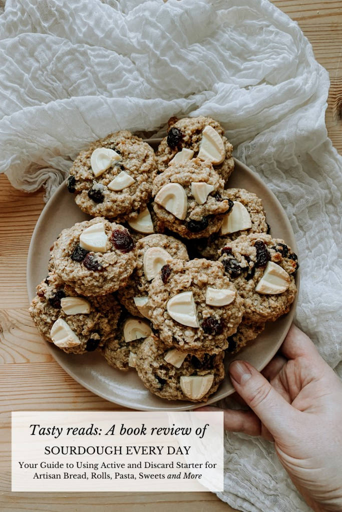 a hand placing a plate of oatmeal cranberry white chocolate cookies on a wooden surface lined with white cloth