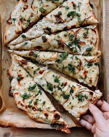 a hand grabbing a slice of Truffled Potato Pizza with Ricotta and Taleggio off of a brown parchment lined baking tray