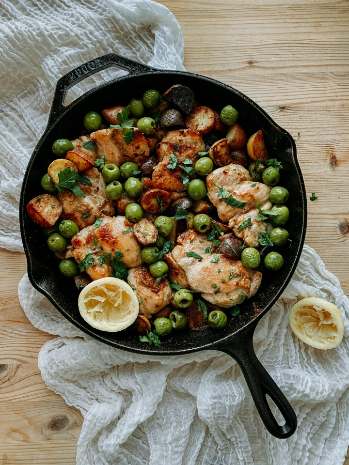 Anchovy Chicken Thighs with Green Olives and Potatoes in a cast iron pan resting on a white towel on a wooden surface