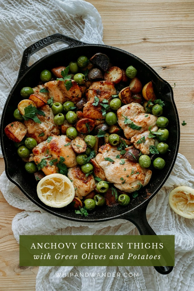 a cast iron skillet with anchovy chicken, potatoes, lemon and green olives resting on a white towel lined wooden surface