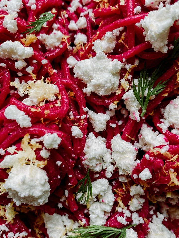 closeup of Pasta with Ricotta Beet Sauce with dill, lemon zest, and goat cheese on top