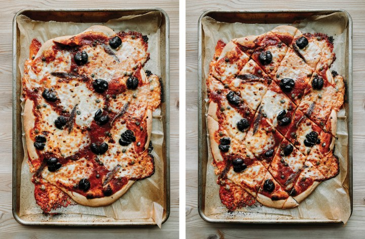 two baking sheets showing an uncut Pizza Puttanesca and the same pizza after it has been cut into pieces